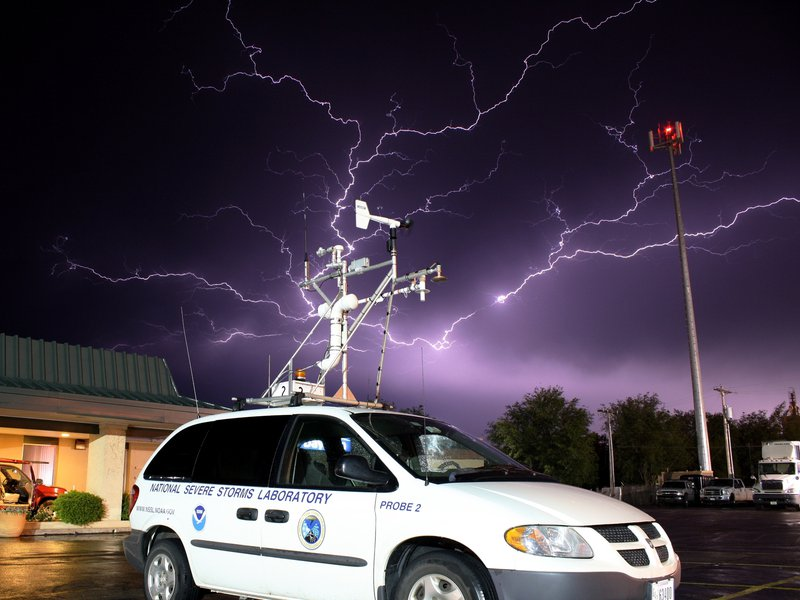 Lightning strike with a stormchase vehicle used in VORTEX2 in the foreground.