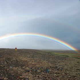 Field scientist under a spectacular rainbow