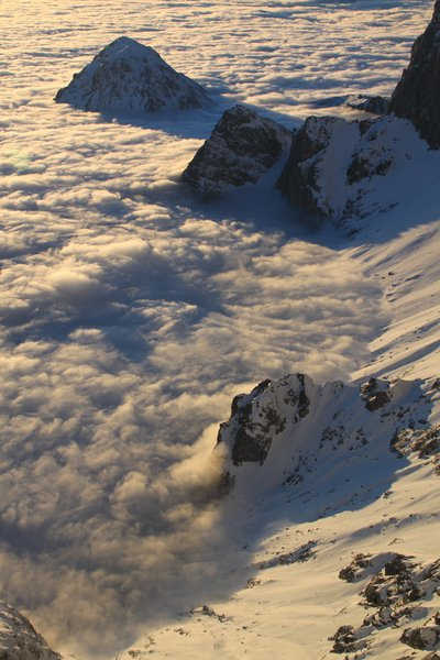 A sea of clouds bracking against snow-covered mountains