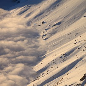 Clouds, snow and the sun on a mountain slope