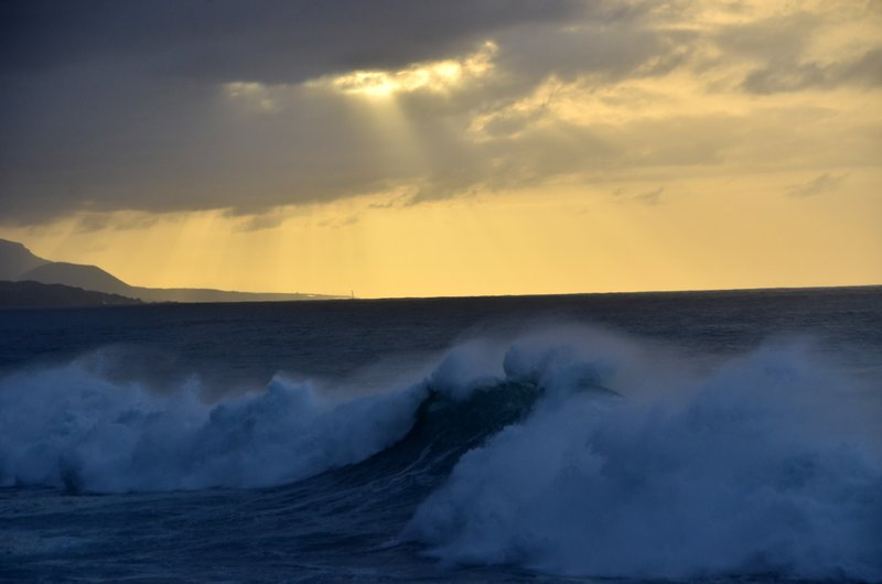 Sun, breaking waves and spray