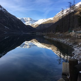 Ceresole Reale ice-free lake acting as a perfect mirror during sunny winter day.